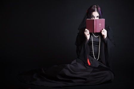A gothic girl with the Bible. Isolated on a black bachground photo