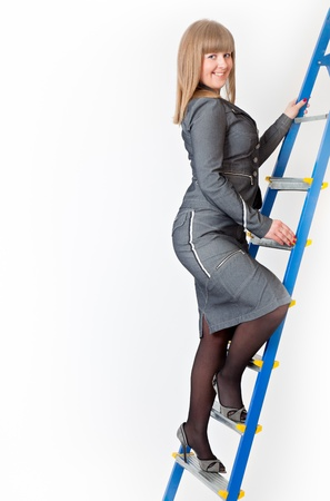 A woman on a stepladder on gray background photo