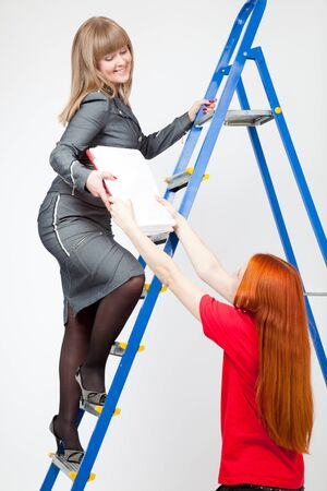Two women on a stepladder with papers on gray background photo