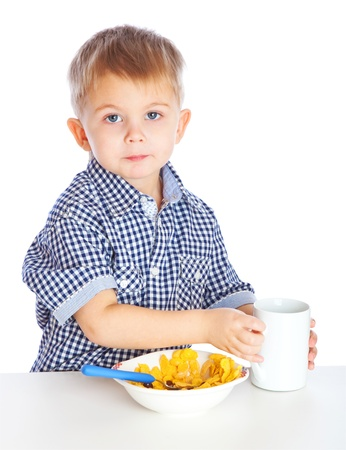 A boy is drinking milk and eating cereal from a bowl. Isolated on a white background photo