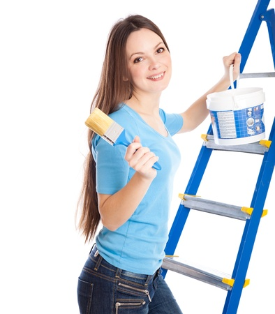 A woman on a stepladder with brush and paint photo