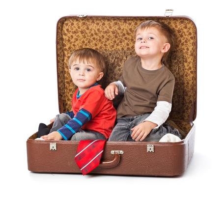 persona viajando: Ni�os en una maleta. Aislado en un fondo blanco