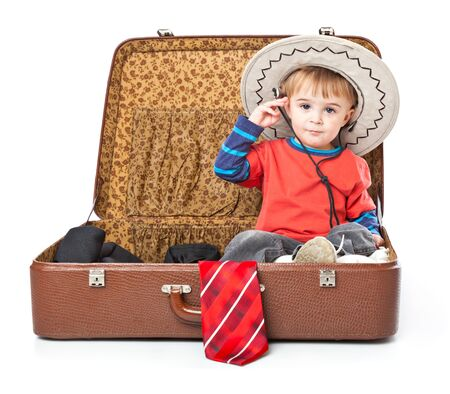 A funny boy with sombrero is sitting in the suitcase. Isolated on a white background photo