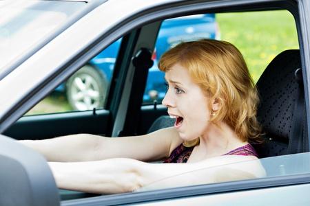 Een bange blonde vrouw achter het stuur van auto