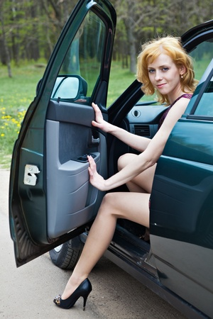 open legs: A beautiful blond woman is sitting in a car Stock Photo