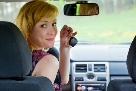 A young smiling blond woman with keys of car photo