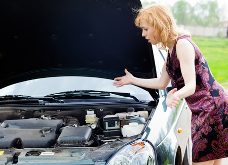 Young blond woman is near a broken car photo