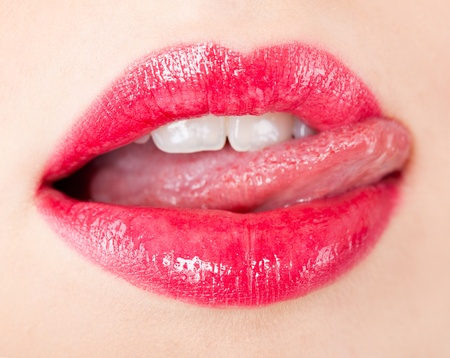Close-up of a female mouth with big red lips and white teeth which she touches with her tongue Stock Photo