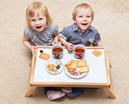 Funny children are sitting on a floor and are eating dessert photo