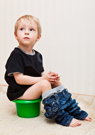 A cute boy is sitting on the pot photo