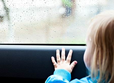 look through window: Little  girl in a car is looking out the window