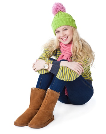 a beautiful girl in a funny cap is sitting on a floor. isolated on a white background photo