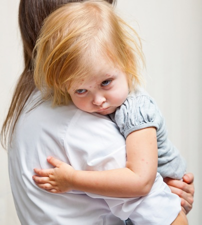 sick girl: a mother is holding tight a sick girl.  Stock Photo