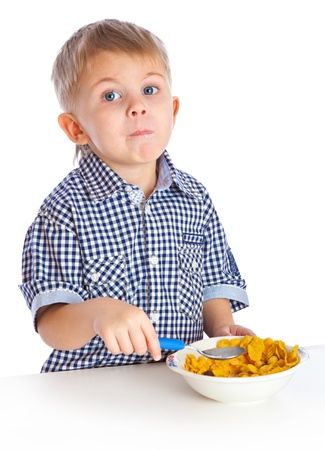 comiendo cereal: Un ni�o est� comiendo el cereal en un plato hondo. Aislado en un fondo blanco