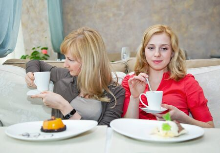 Two young girls are drinking tea in cafe photo