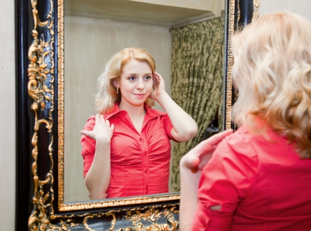 Reflection of young woman in a big mirror