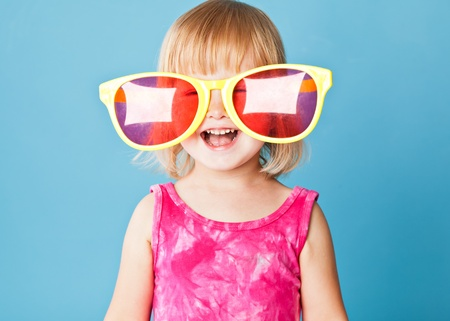 big and small: A little girl with a huge sunglasses on blue background