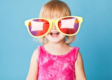 Une petite fille avec un énormes lunettes de soleil sur fond bleu Banque d'images - 9978119