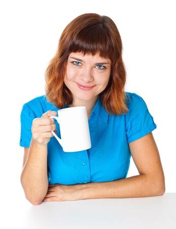 ginger haired: a smiling girl is drinking a coffee from a white cup. isolated on white background