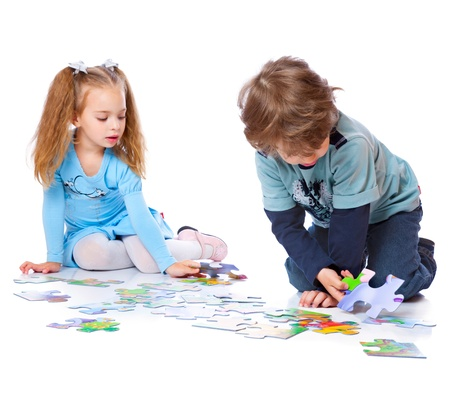 Boy and girl are playing with puzzle. Isolated on a white background