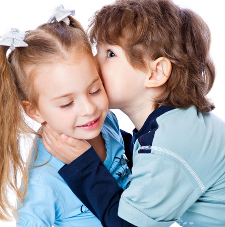 A boy is kissing a little girl. Isolated on a white background Stock Photo