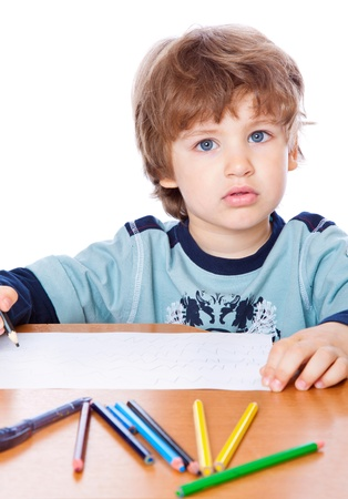A small boy is drawing. Isolated on a white background photo