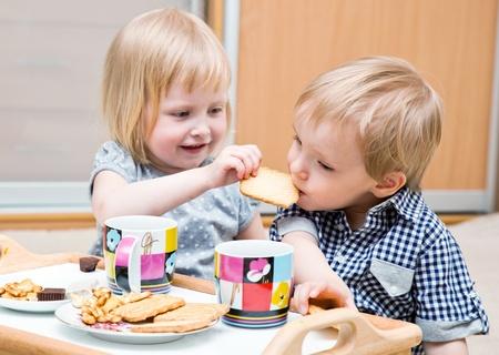 Drôle d'enfants sont assis sur un plancher et un dessert sont manger Banque d'images - 10122061