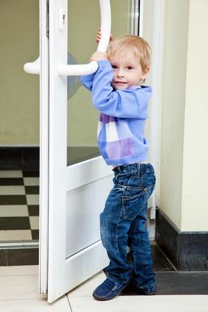 A little boy is opening the door  photo