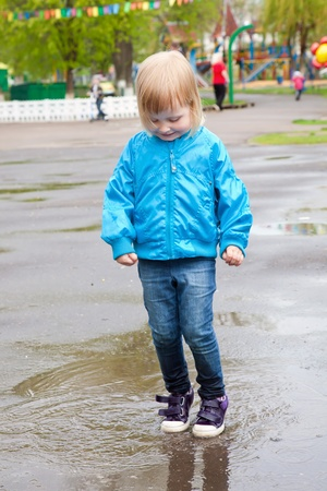 A little girl is jumping in the puddle photo