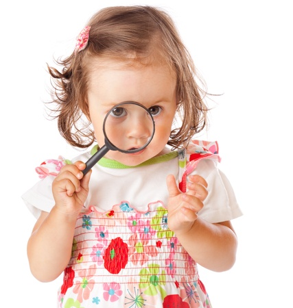 A little girl is looking through the loupe. Isolated on a white background photo