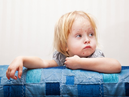 Une petite fille malade est assis près du lit. Banque d'images - 10122025