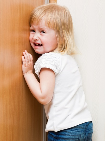 Naughty little girl is standing in the corner photo