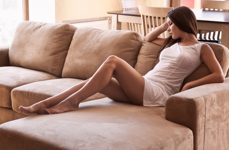 woman couch: Young woman is lying on a couch