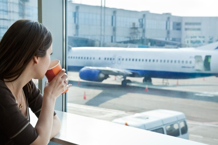 departure board: Young woman is drinking coffee in airport Stock Photo