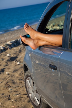 dangling: Womans legs are dangling out a car window Stock Photo