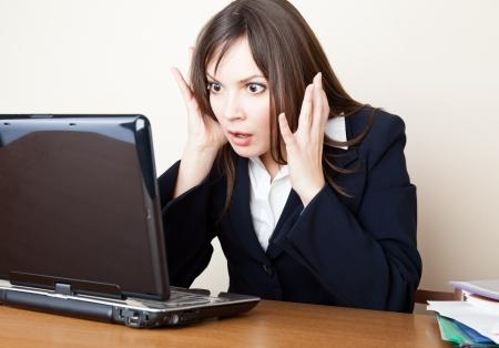 Jonge bange vrouw kijkt naar de laptop scherm