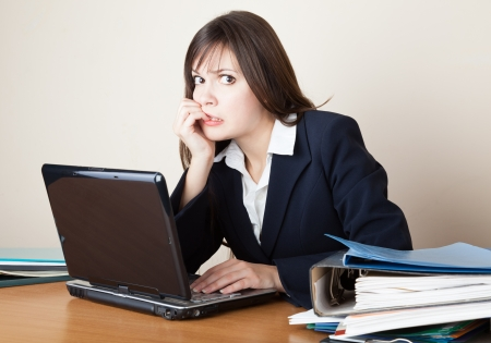 Young frightened woman is looking at the laptop screen Standard-Bild