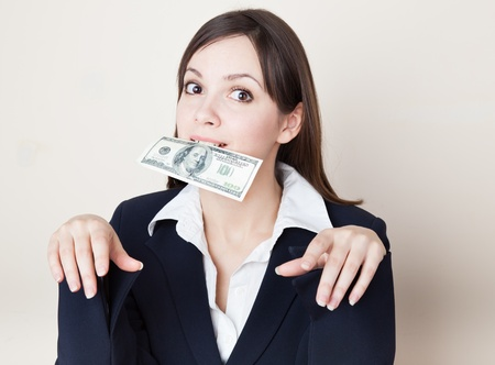 Young brunette woman with 100 dollars in her mouth photo