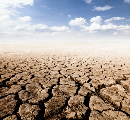 land with dry cracked ground and blue sky