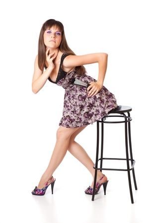 Beautiful girl is sitting on a stool. Isolated on white background Stock Photo - 11269890