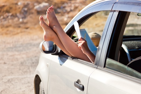 Woman's legs are dangling out a car window. Woman is looking at map