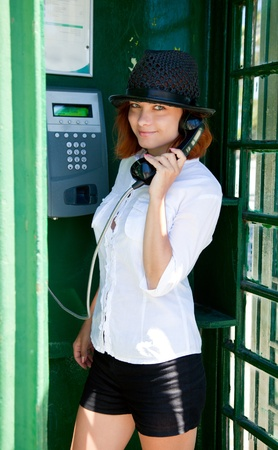 phonebox: Young teenage girl is standing and is speaking in phonebox