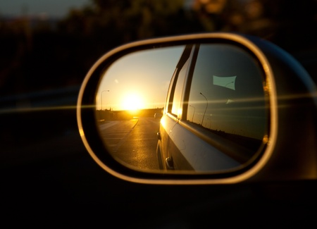 A sunset in the rearview mirror of car as a races down the road. Window of car is opened