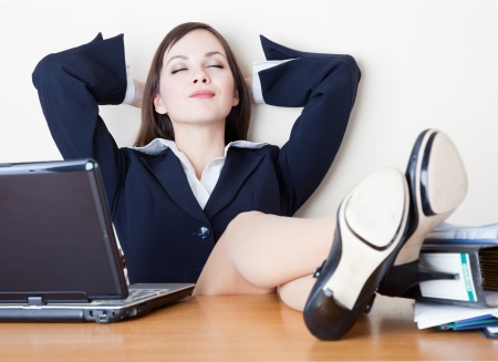resting: The young business woman is relaxing at work Stock Photo