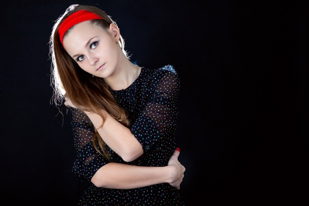 Young teenager girl on black background photo