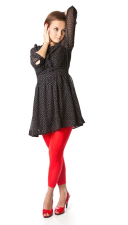 Portrait of teen girl. The girl is wearing black dress and red tights. Isolated on white background photo