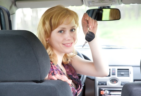 inside car: A young smiling blond woman with keys of car
