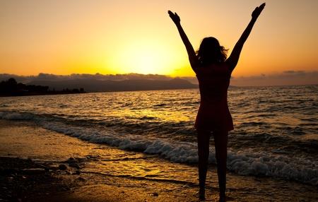 manos levantadas al cielo: Chica delgada joven está disfrutando de la libertad. Puesta del sol y el mar