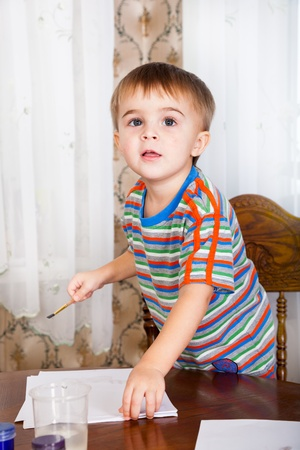 A little funny boy is painting photo
