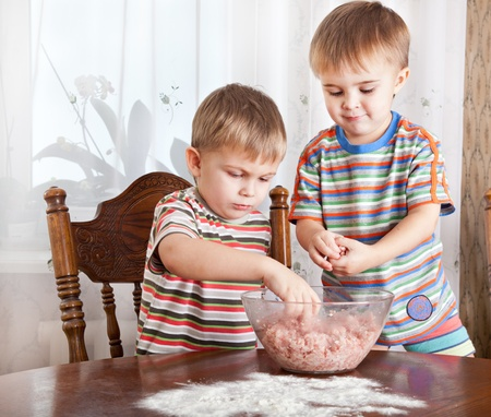 Cute boys are mixing mincemeat in a bowl photo